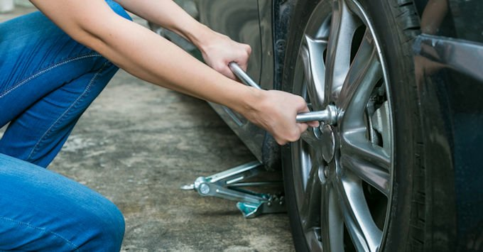Young lady fixing a flat tire